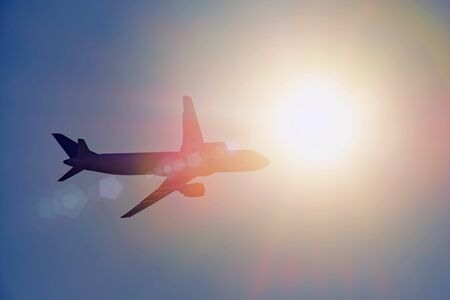 Airplane silhouette flies against the bright sun with glare