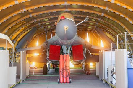 Wing military fighter with folded wings in the garage of the hangar on service repair Stockfoto - 129844104