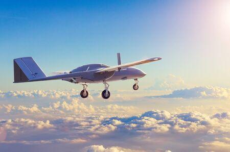 Uav de reconnaissance d'avions militaires sans pilote patrouillant le soir au coucher du soleil les nuages du ciel