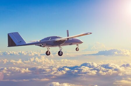 Unmanned military aircraft reconnaissance uav patrolling the evening at sunset sky clouds