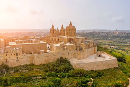 St. Pauls Cathedral in the town of Mdina surrounded by a fortress narrow streets, aerial view