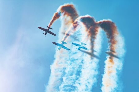 Three light-engine aircraft perform aerobatics - a dead loop. The bright sun illuminates the planes and the shadows fall on the smoke they leave in the sky