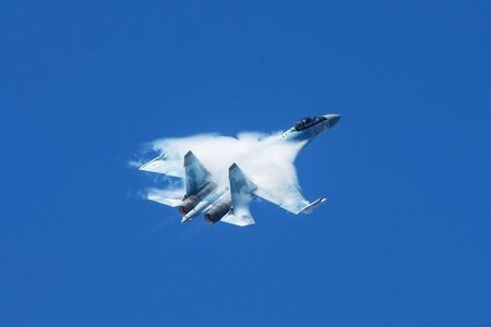 Air Force fighter jet performs a sharp maneuver in the sky, the pressure drop behind the wing causes visible vapor condensation