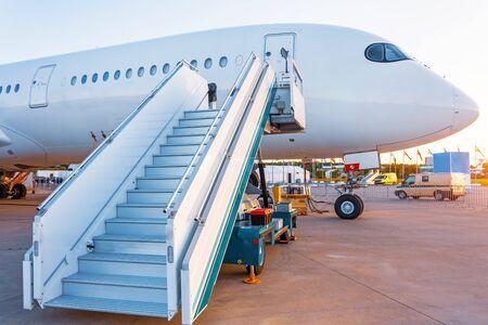 Atardecer vespertino ver la nariz de la aeronave, escalera a la entrada de la aeronave en el estacionamiento del aeropuerto Foto de archivo