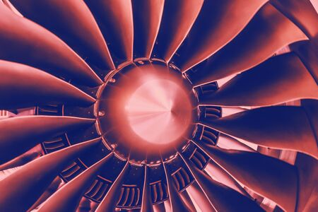 Close up of a turbofan turbine blades jet engine in modern airplane with pink and blue gradient toned