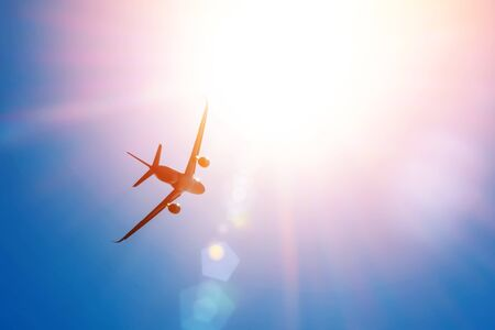 Bright sun in the sky and a flying passenger plane in height. The concept of tourism, vacation, travel Banco de Imagens
