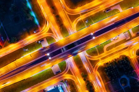 Highway and large bridge with road junction illuminated by lanterns at night, markings on asphalt are visible, night aerial top view Stock Photo