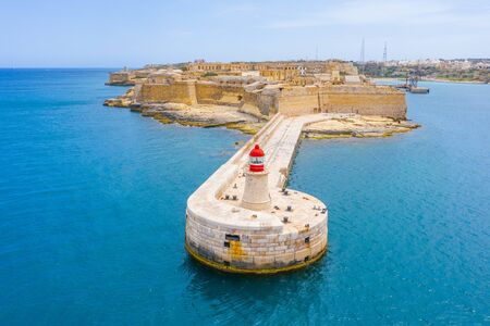 Lighthouse on the artificial cape of the pier in Valletta Bay Malta