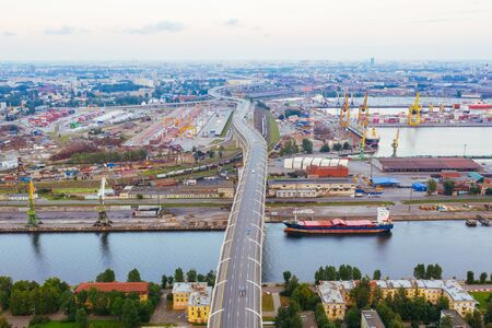 Freeway over the industrial area of the city and the sea channel, aerial top view