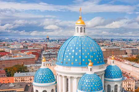 The famous Trinity Cathedral with blue domes and gilded stars, view of the historic part of the city of Staint-Petersburg, typical houses around