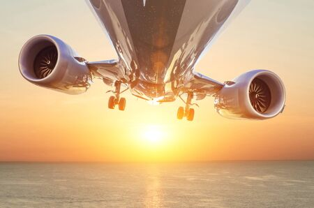 Airplane with landing gear lowered before landing flies at sunset over the sea Banco de Imagens