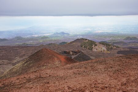 Volcanic landscape with frozen lava fields in cloudy weather on mountain peaks