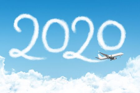 Happy New year 2020 concept travel on the background below cloudscape. Drawing by passenger airplane vapor contrail in sky Banco de Imagens