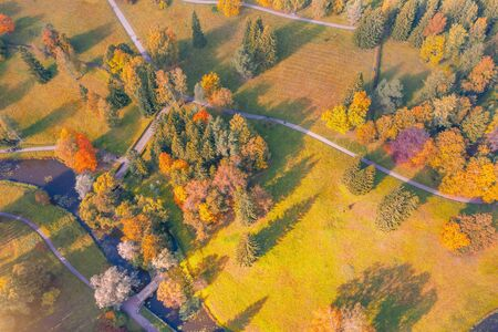Aerial view flight over autumn valley park with meadows and a winding river with bridge, bright trees