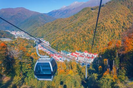 Cableway with ski lifts and cabins for tourists, a view of the town and the autumn forest in the mountains of the Caucasus