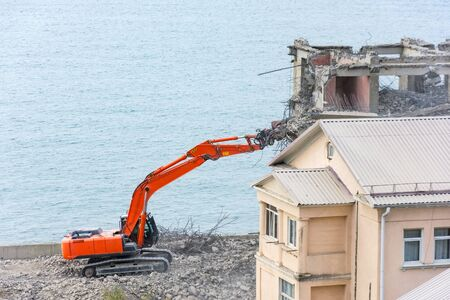 Excavator with hydraulic shears against the background of a demolished building. Dismantling of emergency construction