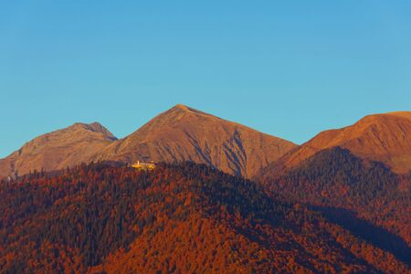 Evening light on the three peaks of the mountains on the slopes of the autumn forest Banco de Imagens