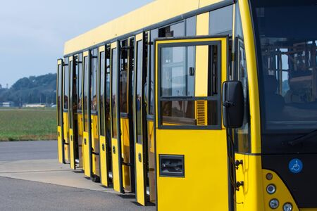 Yellow passenger bus with open doors waiting for passengers to transport to the plane at the airport