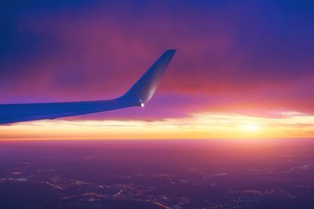 Sunset sky from an airplane side wing view of the horizon and city lights