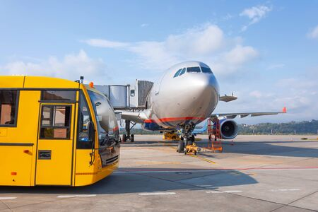 Shuttle yellow bus waiting for passengers on the plane for transportation to the airport terminal. Aircraft arrival background. Travel tourist destination concept Reklamní fotografie