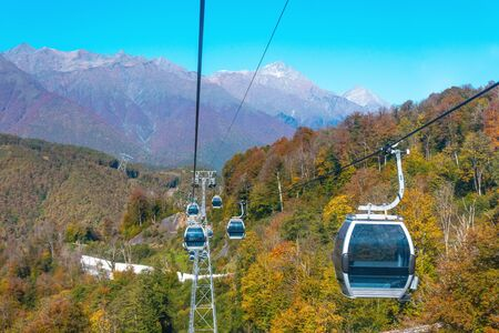 Cableway with ski lifts and cabins for tourists, a view of the town and the autumn forest in the mountains Banco de Imagens