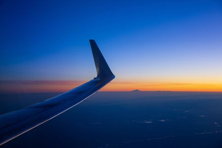 View of the wing of an airplane before dawn. Mountains and a peak are visible in the distance Stock fotó