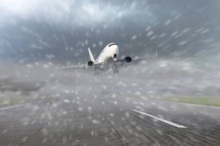 Airliner taking off from the runway at the airport during bad weather, low visibility, snow. Concept of delayed or late flights
