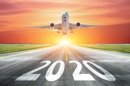 The inscription on the runway 2020 surface of the airport runway with take off airplane. Concept of travel in the new year, holidays Reklamní fotografie