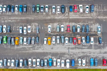 Aerial view from above of the parking lot with cars in the business district of the city, wet asphalt