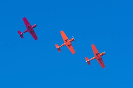 Three light-engine turboprop red aircraft fly in formation in a straight line in the sky Reklamní fotografie