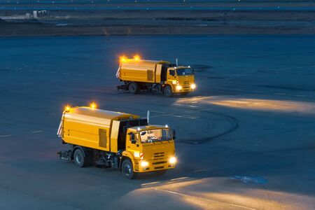 Trucks for cleaning garbage from roads at the airport, at night
