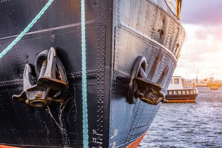 The nose and anchors of a black icebreaker moored in the port