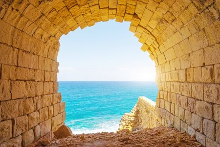 Ancient stone arch overlooking the blue tropic sea