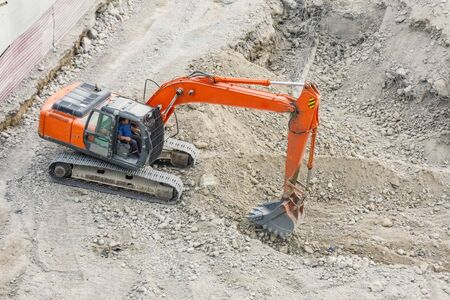 Red excavator digs rocky soil, top view