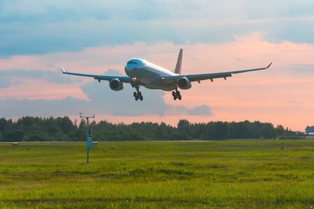 Passenger airplane landing on runway at airport, early evening