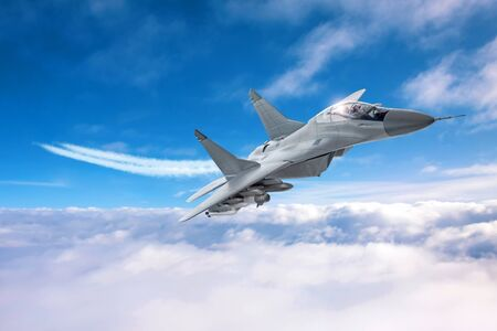 Military airplane speed flies with a smoky train low above the clouds