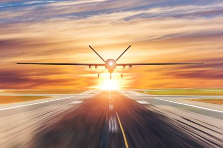 Military unmanned aerial vehicle takes off from runway at a military base in the evening at sunset