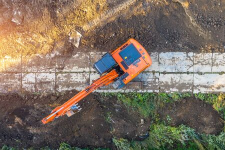 Excavator on caterpillars in the foundation pit during the construction of the building foundation, digging. Aerial top view
