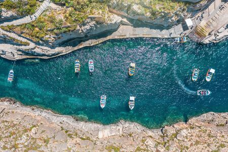 Narrow bay with pleasure boats among the rocks, aerial view