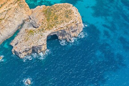 A rock with an arch cave in the blue azure sea, aerial view 스톡 콘텐츠