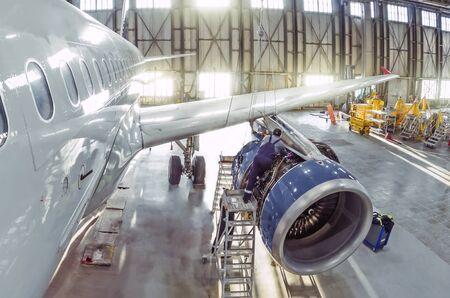 A working mechanic is repairing a passenger plane engine in a hangar 스톡 콘텐츠