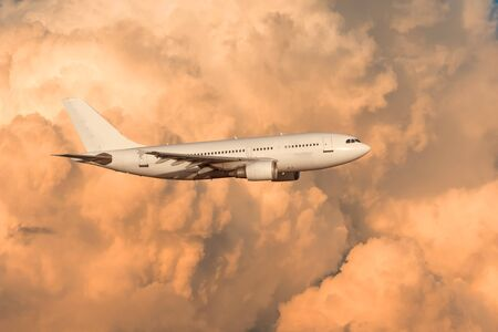 The plane flies on powerful cumulus clouds lit by the setting sun