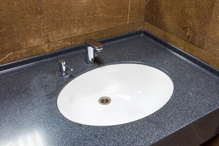White sink in brown marble countertop with chrome shiny faucet and integrated dispenser for liquid soap 版權商用圖片