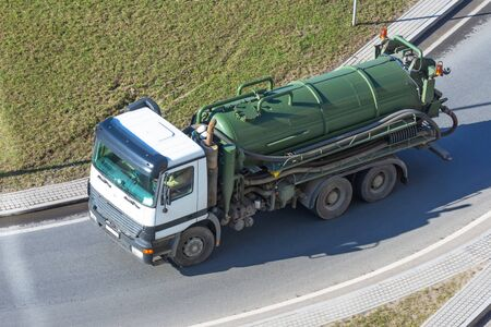Truck with green tank for pumping waste or contaminated water Stock Photo