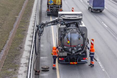 Sludge washer truck and workers specialists at work on the side of the highway to clean underground infrastructure, eliminate blockages in the sewer road sewage into the collector