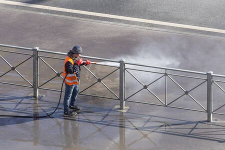 Worker cleaning driveway with gasoline high pressure washer splashing the dirt, asphalt road fence. High pressure cleaning