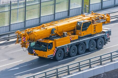 Heavy mobile crane with folding boom construction rides on a city highway Stock Photo