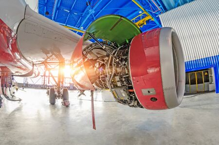 View under the wing of the landing gear of a passenger airplane, open engine hood of the aircraft