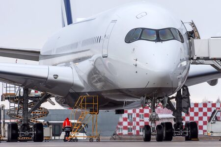 Wide-body aircraft at the airport parking lot, view of the cockpit and landing gear Stock Photo