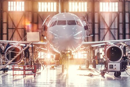 Airplane under repair in the aerospace hangar in the background of the gate and bright sunlight